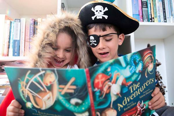 Kids dressed as pirates and reading a pirate-themed book.
